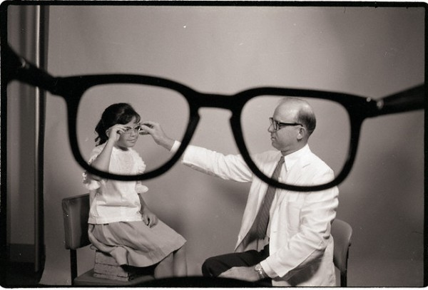"30 Mar 1963 --- Original caption: 3/30/1963-New York, NY-: Appropriately ""framed,"" Dr Charles Behran, of the Manhattan Eye and Ear Hospital, fits Toni Garcia, of New York City, with a pair of eyeglasses. This hospital is one of the many outlets for New Eyes For The Needy, Inc. By various arrangements, New Eyes pays for glasses in 43 states for screened patients to whom no other private or public funds are available. This is in addition to its work abroad. --- Image by © Bettmann/CORBIS"